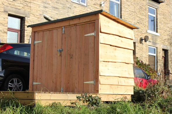 Shed made out of reddish softwood with a clapboarded sides.