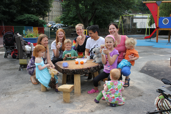 Kids and grownups around a little table in a playpark