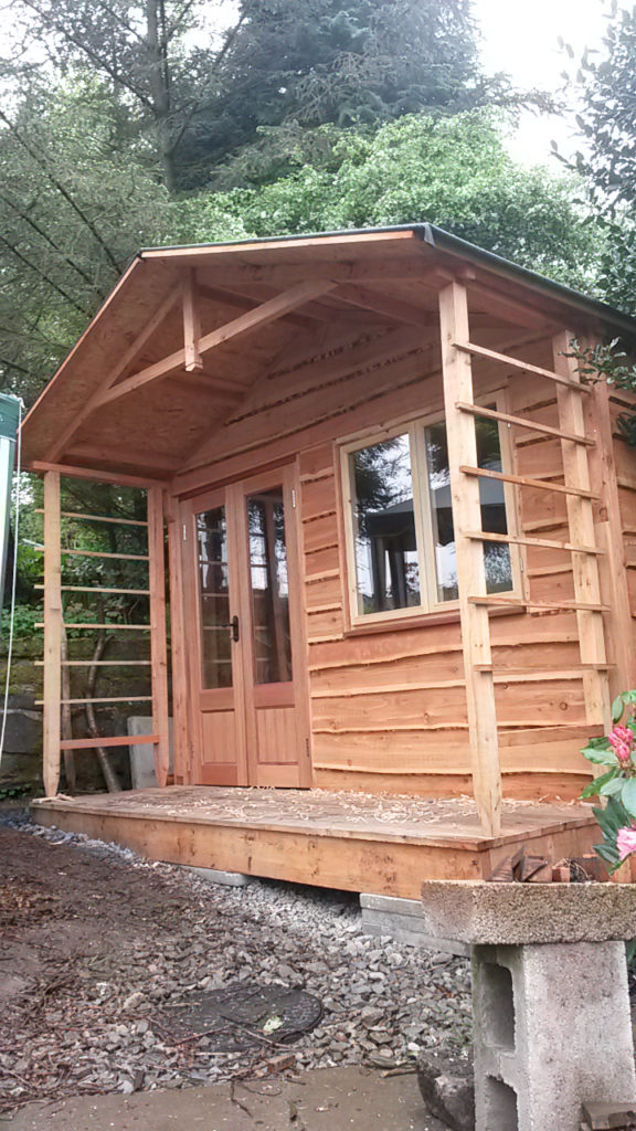 Pticture of a timber clad studio with a porch and trellis